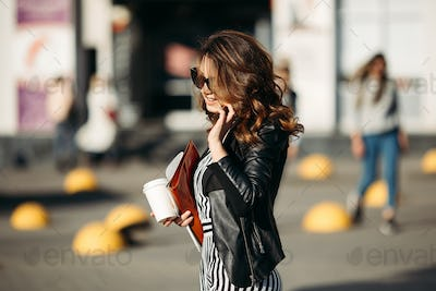 Beautiful brunette walking at street and talking to phone
