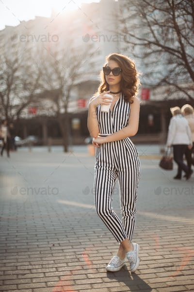 Gorgeous woman walking at street with cup of coffee