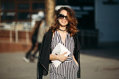 Smiling fashionable brunette walking at street