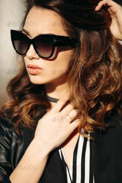 Fashionable brunette woman with volumed haircut seductive posing