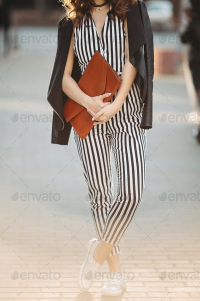 Stylish spring look with striped overalls and leather jacket