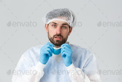 Covid-19, pandemic, healthcare workers fighting virus outbreak. Tired bearded doctor take-off