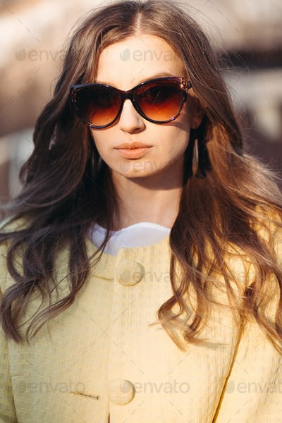Brunette woman in sunglasses and yellow coat