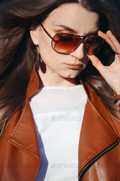 Bbeautiful girl wearing in leather jacket undressing sunglasses