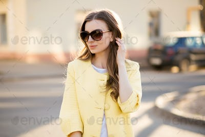 Fashionable and stylish woman in sunglasses and yellow coat