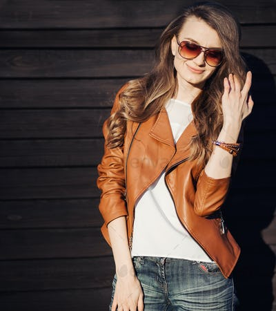 Smiling woman in sunglasses and leather jacket posing at street