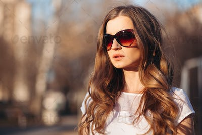 Beautiful seductive woman in sunglasses walking at street