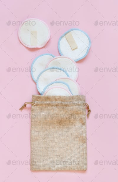 Eco friendly reusable make-up remover pads in a bag on pink background