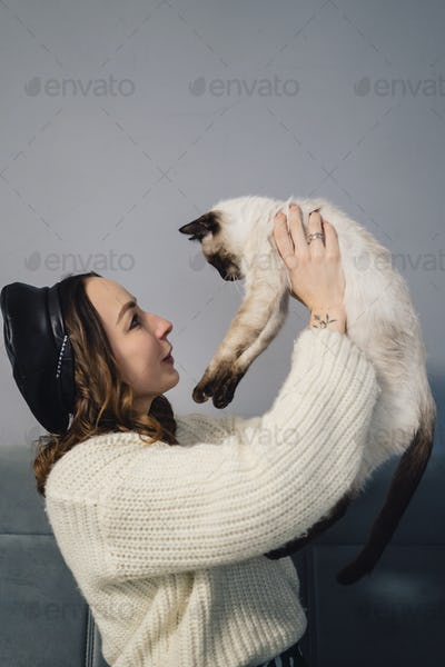 Pretty woman playing with siamese cat