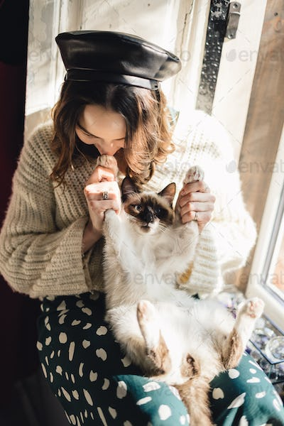 Pretty woman holding her cat paws stretching