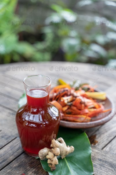 wedang uwuh drinks in glass bottles and red ginger, secang shaved wood, lemongrass in pottery plates