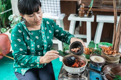 Asian woman selling herbal medicine pouring herbal concoctions into a pot