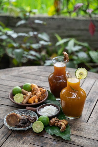 Herbal drinks of beras kencur and kunyit asam are packed in glass bottles serving with raw materials