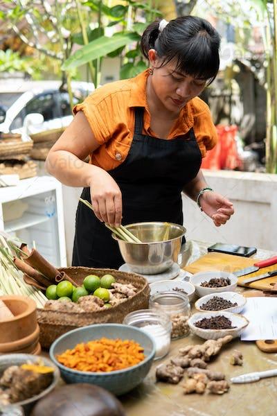 asian woman jamu maker