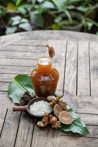 Herbal drinks of beras kencur are packed in glass bottles serving with raw materials