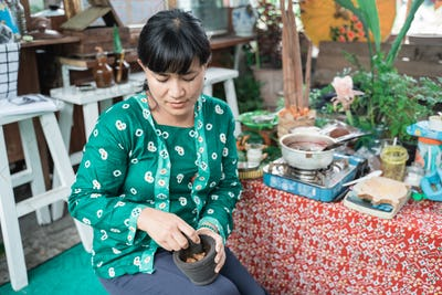 woman selling herbal medicine masses using mortar