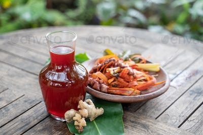 red herbal drinks and raw materials in a pottery plate