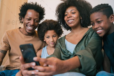 Family taking selfie together with phone at home.
