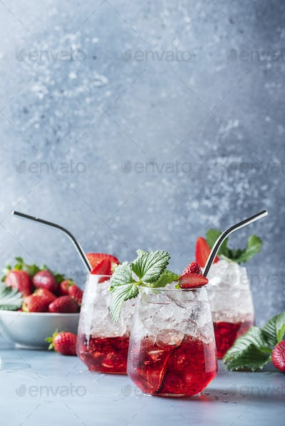 Red cocktail with ice and fresh strawberry