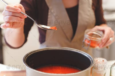 Female cook adds paprika spices while cooking tomato soup.Close-up view on spoon with red pepper.