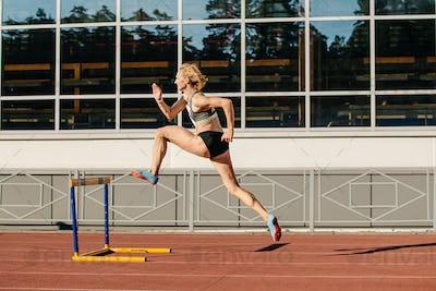 female athlete run 400 meters hurdles