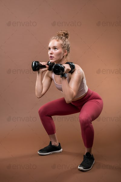 Young strong sportswoman in tracksuit sitting on squats and lifting dumbbells