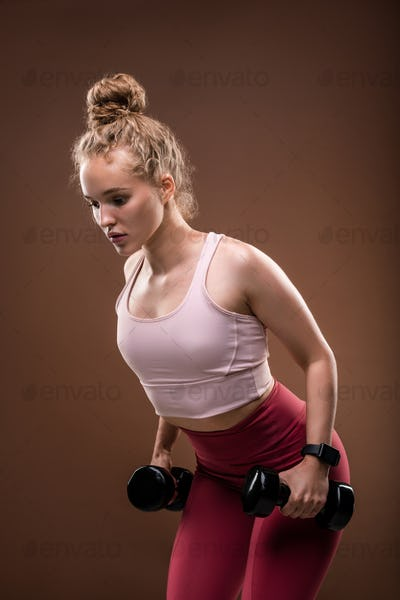Young blond female in tracksuit bending slightly forwards while doing exercise