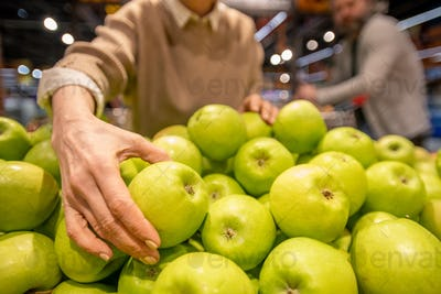 Hand of mature female consumer choosing fresh granny smith apples