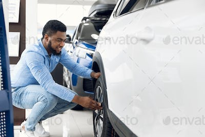Black Guy Checking Car Wheels And Tyres In Dealership Showroom