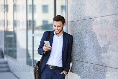 Confident enterpreneur checking messages on his mobile phone near office building wall in city