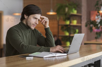 Concentrated guy working on big project online