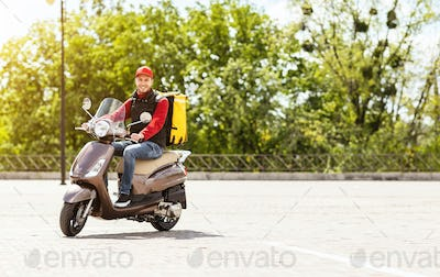Courier Delivering Food In Box Riding Motorbike Outdoors