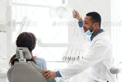 African dentist starting session with female patient