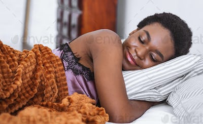 Enjoy in bed. Smiling african american girl with closed eyes, lies