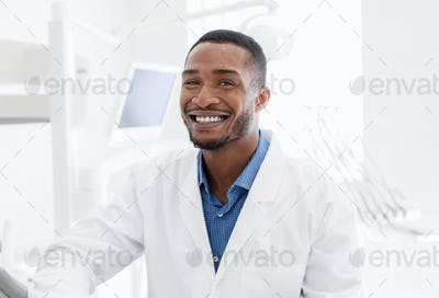 Handsome black dentist smiling over modern dental clinic background