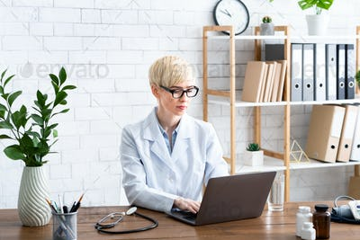 Healthcare concept. Woman doctor working on laptop at table