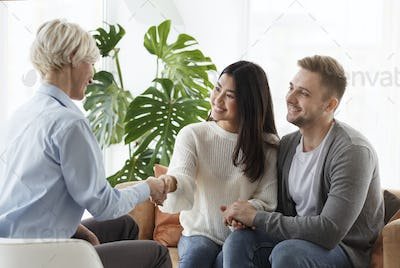 Couple Shaking Hands With Counselor Thankful For Help In Office