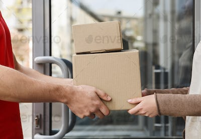 Guaranteed excellent service. Hands of client and courier are holding parcels