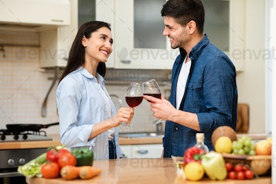 Lovely couple drinking wine together in kitchen at home