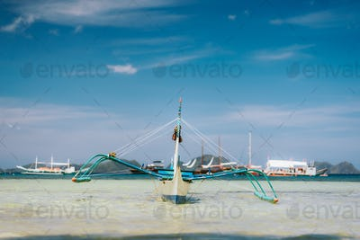 Traditional banca boat in clear water at sandy Corong Beach in El Nido, Philippines. Low angle view