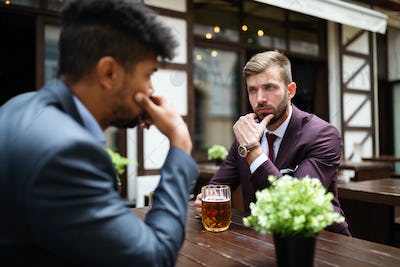 Two sceptical business men talking on a meeting outdoor