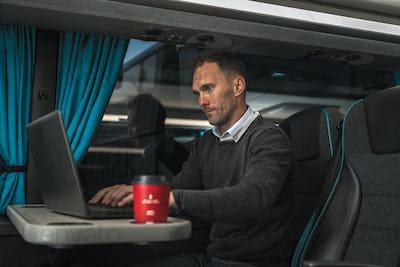 Businessman Working on His Laptop Inside Coach Bus on Long International Haul.
