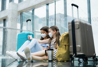 Small children with smartphone going on holiday, wearing face masks at the airport
