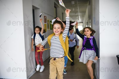 Group of cheerful children going home from school after covid-19 quarantine and lockdown