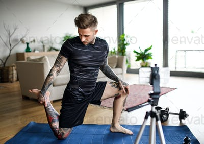 Man trainer doing online workout exercise indoors at home, using camera