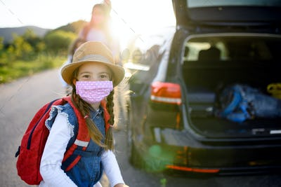 Small girl with family on trip outdoors in nature, wearing face masks