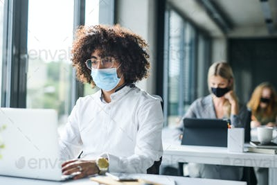 Portrait of young man with face mask back at work in office after lockdown