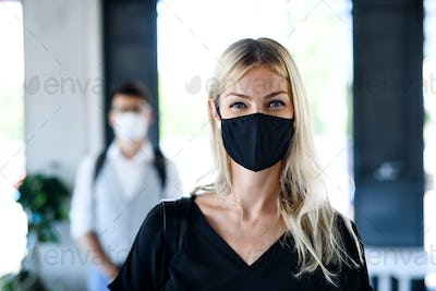 Young woman with face mask back at work in office after lockdown, looking at camera