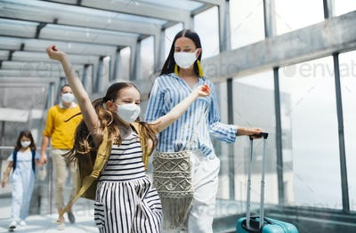 Family with two children going on holiday, wearing face masks at the airport
