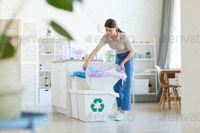 Woman sorting trash in the bins